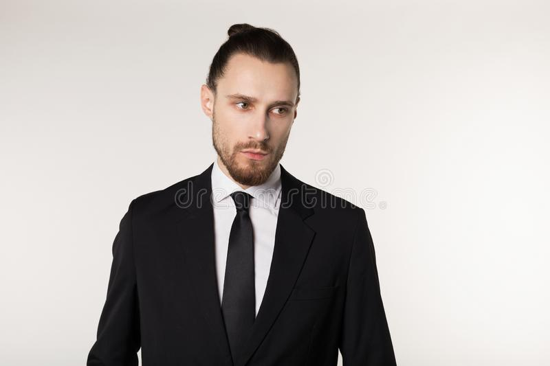 Half length portrait of beautiful brunette bearded guy with trendy hairdo in black suit royalty free stock image