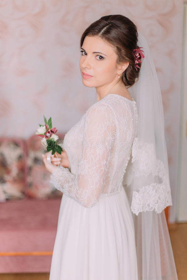 Half-length portrait of beautiful sensual young bride in wedding dress looking over her shoulder indoors holding royalty free stock photos