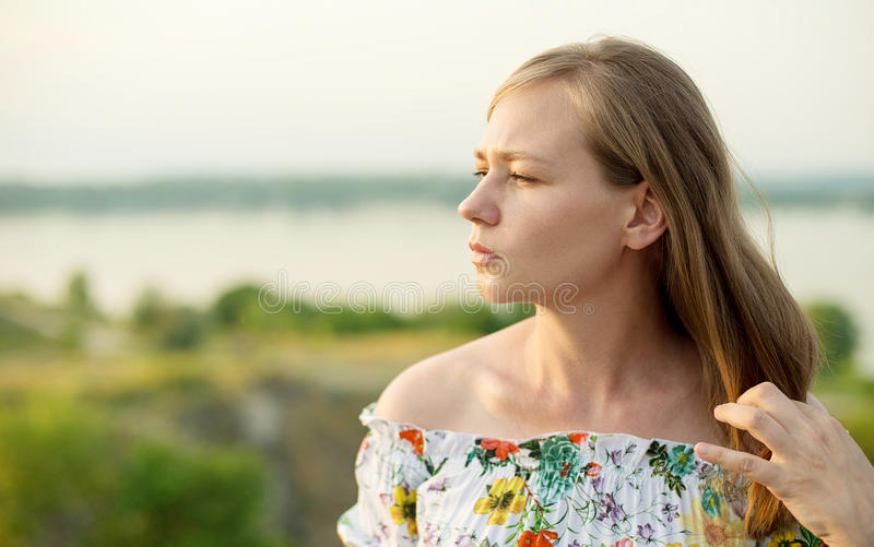 Half length portrait of charming positive woman is looking epically off into the distance in sunset background.  stock images