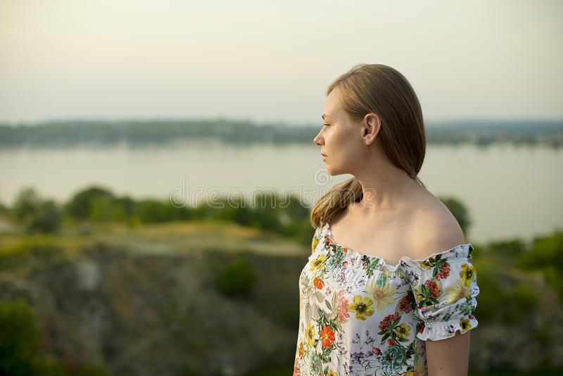 Half length portrait of charming positive woman is looking epically off into the distance in sunset background.  royalty free stock images
