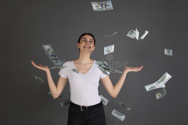 Half length portrait of cheerful glad girl in white t-shirt enjoying shower from 100 hundred dollars. Flying money, gesturing with hands on grey background royalty free stock images