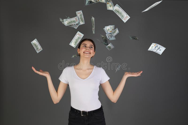 Half length portrait of cheerful glad girl in white t-shirt enjoying shower from 100 hundred dollars. Flying money, gesturing with hands on grey background royalty free stock photography