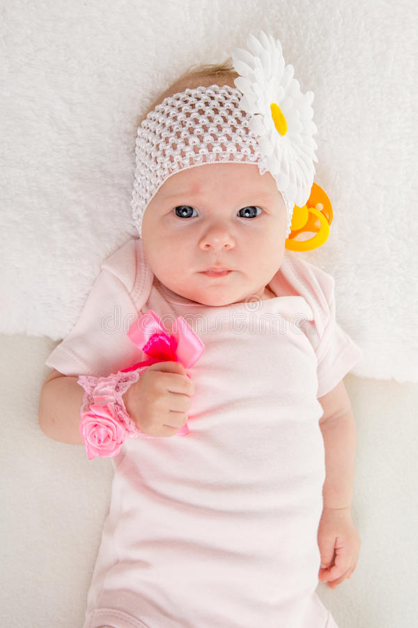 Half-length portrait lying old girl. A two-month baby girl Europeans on the back with a bandage on his head with a flower lying on a soft bed stock photos