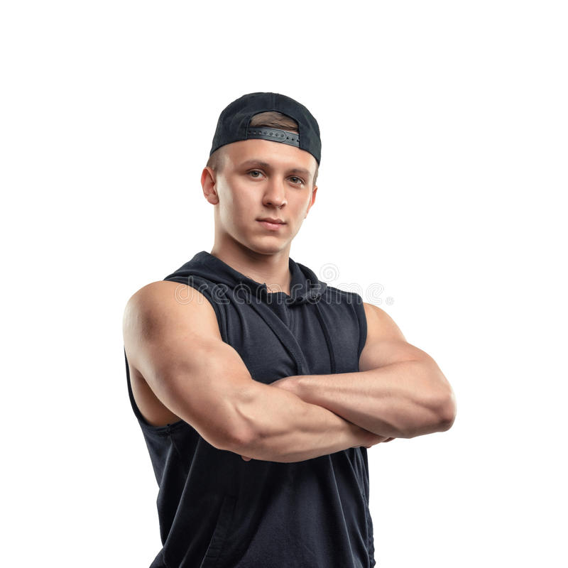 Half-length portrait of muscled young man stands with folded arms. Healthy lifestyle. Fitness and sport. Youth and strength royalty free stock photo