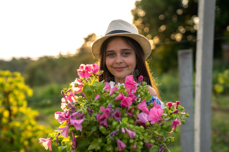 Half length portrait of smiling cute little girl with healthy skin in white hat and dress that holding a large bouquet stock photography