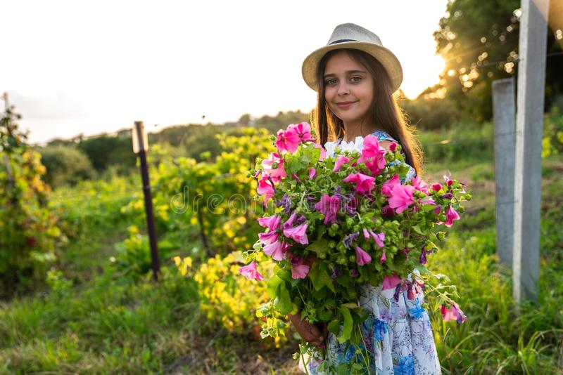 Half length portrait of smiling cute little girl with healthy skin in white hat and dress that holding a large bouquet stock images