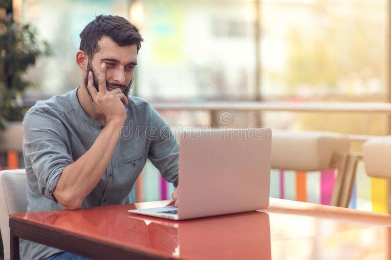 Half length portrait of successful bearded designer smiling at camera while working on freelance at netbook. stock photography