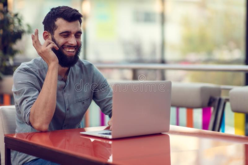 Half length portrait of successful bearded designer smiling at camera while working on freelance at netbook. royalty free stock photos