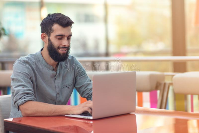 Half length portrait of successful bearded designer smiling at camera while working on freelance at netbook. royalty free stock photo