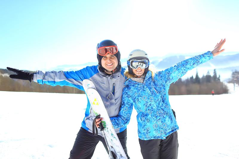 Half-length portrait of two embracing skiers who wear goggles and sports jackets. selective focus.  royalty free stock photo