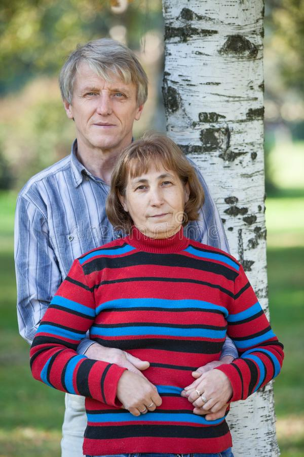 Half-length portrait of two pension age people standing together near birch, man embracing his woman. Half-length portrait of two pension age people standing royalty free stock images