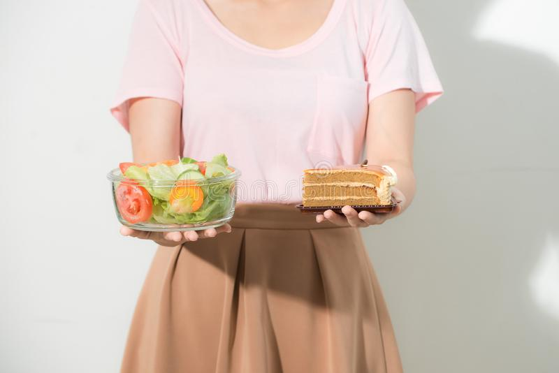 Half-length portrait of very beautiful woman holding small cake, fresh vegetables. Young housewife choosing sweets or healthy stock images