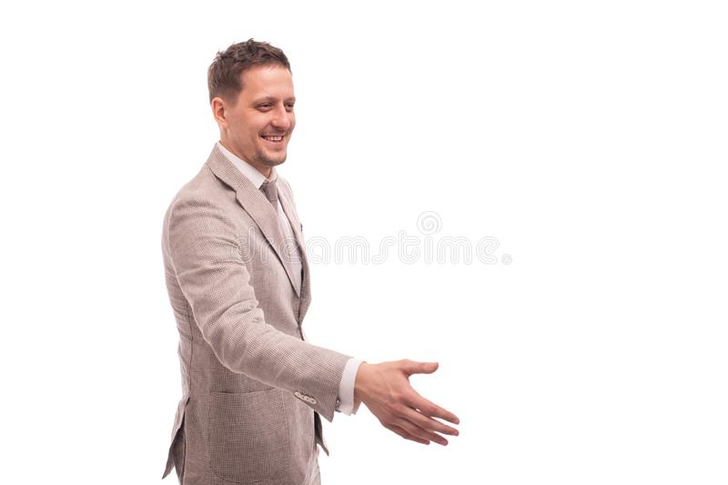 Half length portrait of a young man wearing beige suit , isolated. He welcomes someone to reach out for a handshake. stock image
