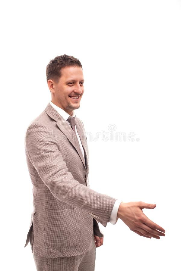 Half length portrait of a young man wearing beige suit , isolated. He welcomes someone to reach out for a handshake royalty free stock image