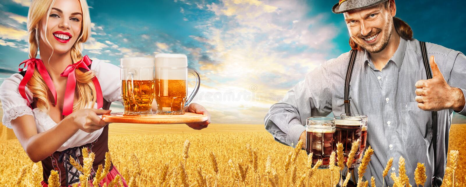 Portrait of Oktoberfest man and woman, wearing a traditional Bavarian clothes, serving big beer mugs. stock photography