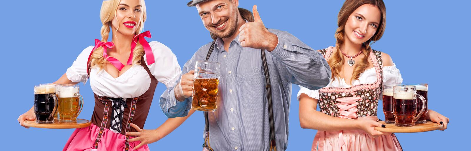 Portrait of happy Oktoberfest man and two women, wearing a traditional Bavarian clothes, serving big beer mugs on blue stock images