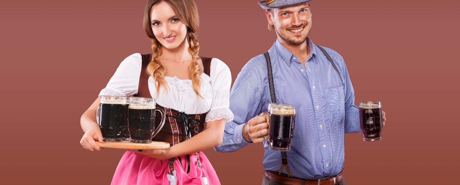 Portrait of happy Oktoberfest man and woman, wearing a traditional Bavarian clothes, serving big beer mugs on brown royalty free stock photo