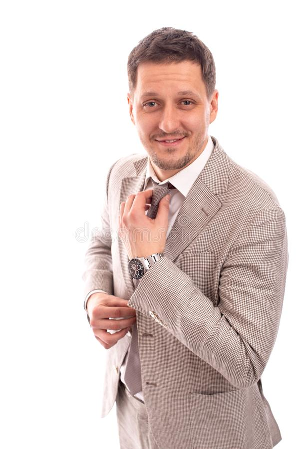 Half length portrait of young positive smiling man straightening his tie against a white background royalty free stock images