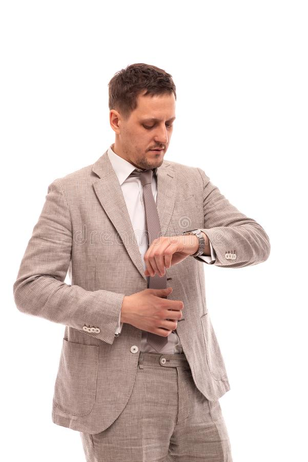 Half length portrait of a young serious man wearing beige suit , isolated. He looks at his watch stock photos