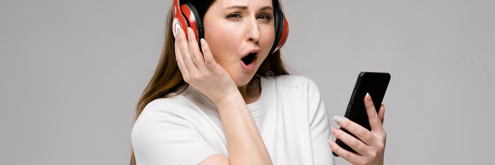 Portrait of emotional beautiful happy plus size model in headphones looking in camera holding mobile phone listening to royalty free stock photography