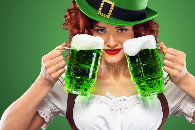 St Patricks Day. Young Oktoberfest waitress, wearing a traditional Bavarian dress, serving big beer mugs on green royalty free stock images