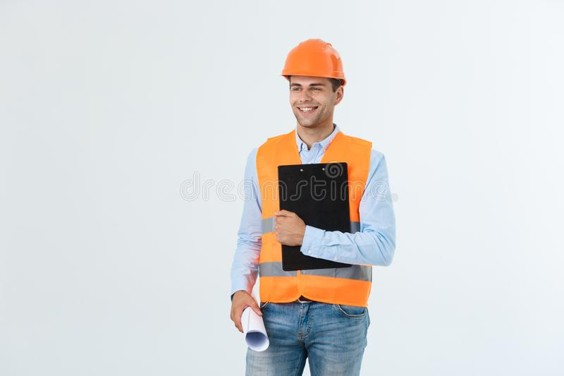 Half-length portrait of young smiling handsome architect engineer in orange helmet posing with blueprints looking at stock image