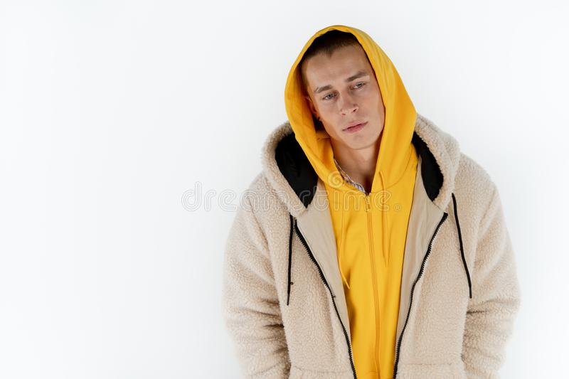 Half length portrait of young upset unhappy man wearing yellow hoodie standing against white background, copyspace for stock photo