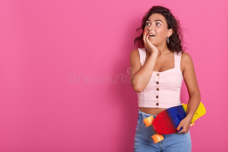 Half length shot of happy surprised curly woman, spending time with friends, ready for riding skateboard together, wears rosy t. Shirt and jean, posing with stock images