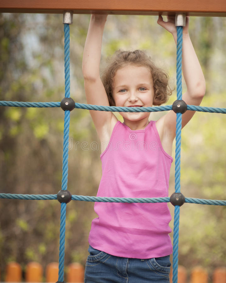 Half-length shot of young girl on climbing net stock photography