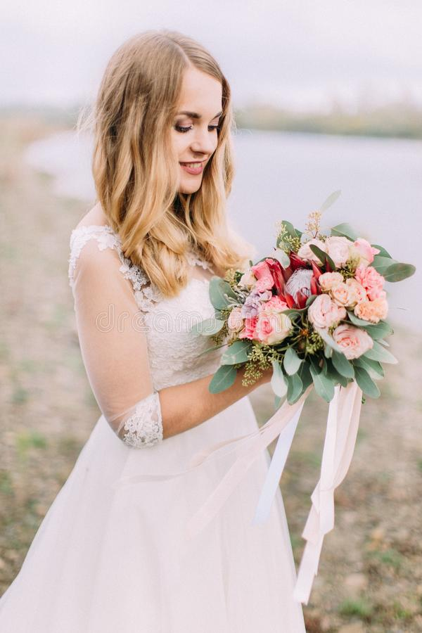 Half-length side portrait of the blonde bride holding the wed bouquet on the beach. stock images