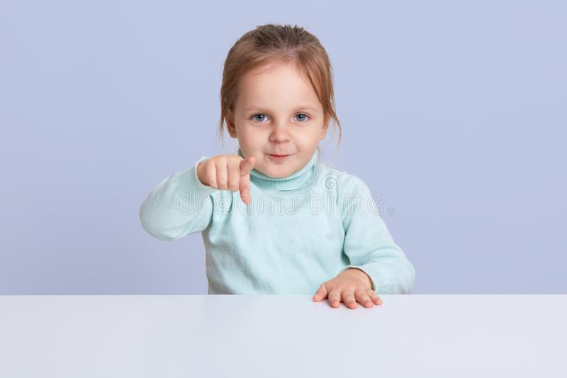 Half length studio photo of charming little girl wearing casually, pointing directly at camera, showing something to her mother,. Choosing doll, model posing stock photos