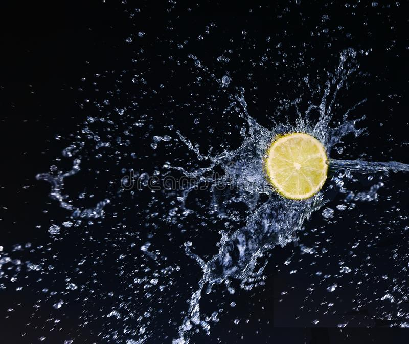 Half a lime falling into the water isolated. On a black background stock images