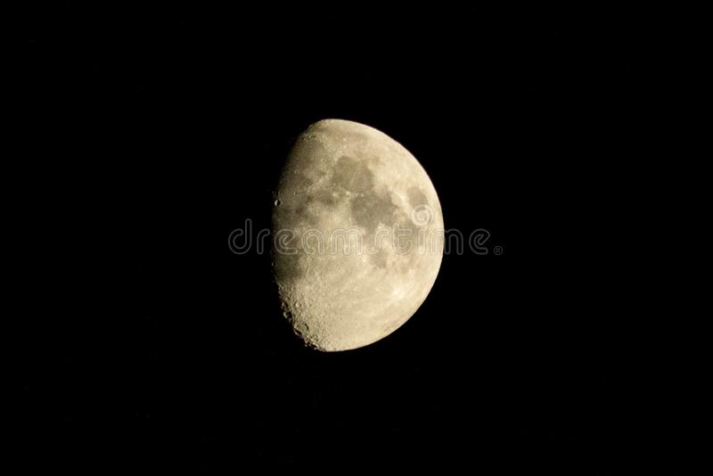 Half lit moon showing craters and surrounded by black sky taken from Radcliffe, England royalty free stock photos