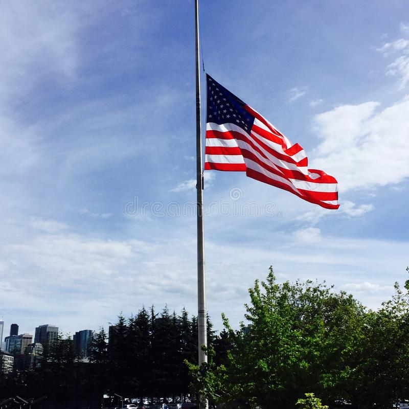 Half Mast American Flag in Bright Blue Sky royalty free stock images