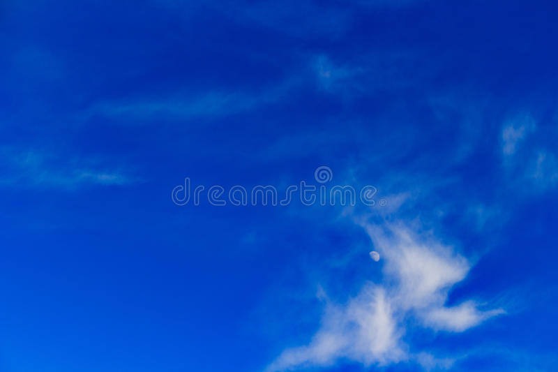 Half moon amidst wispy clouds stock photo