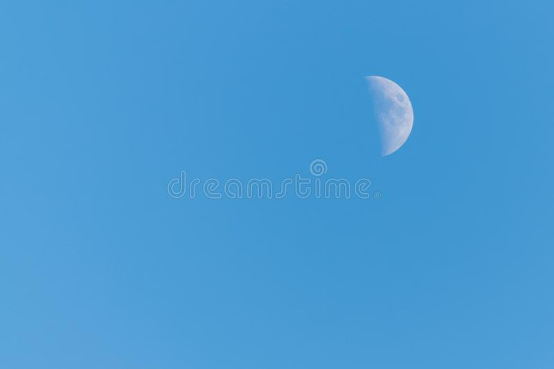 Half moon on a clear blue sky stock images