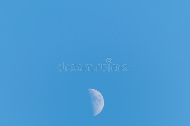 Half moon on a clear blue sky royalty free stock image