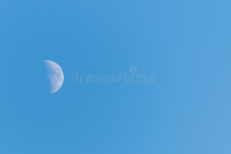 Half moon on a clear blue sky royalty free stock images
