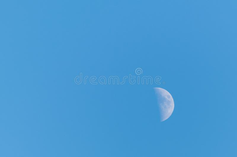Half moon on a clear blue sky royalty free stock photography