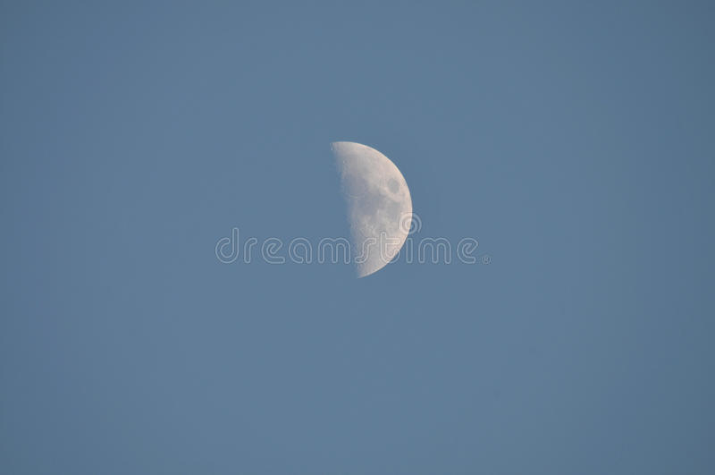Half Moon in Daytime Sky. Close up of half moon in the daytime sky with blue background royalty free stock images