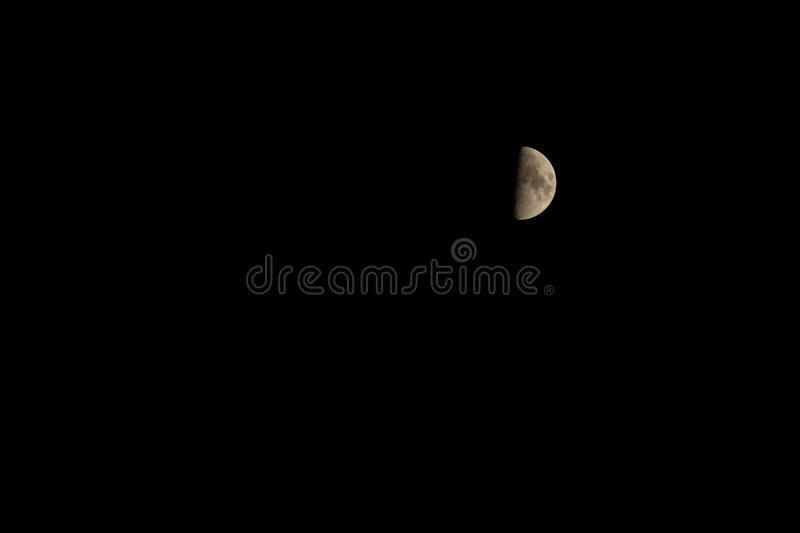 Half moon. At night half moon with craters on a black clear sky background. Satellite orbiting Earth royalty free stock images