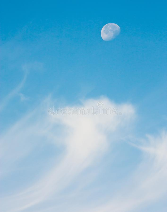 A half moon riding in the sky above wispy cirrus clouds stock photos