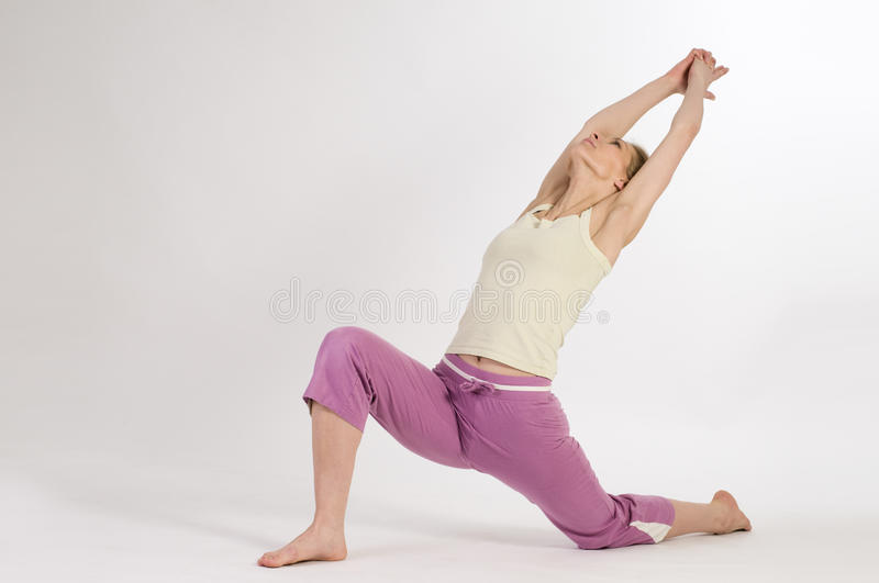 Half moon right. Blond woman in yoga position half moon on white background royalty free stock photography