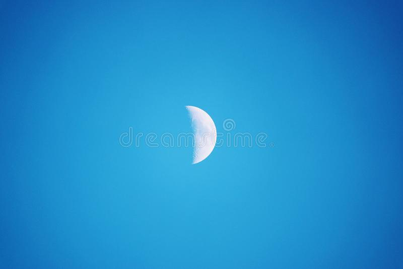 Half Moon Seen in the Daytime, In a Blue Sky stock images