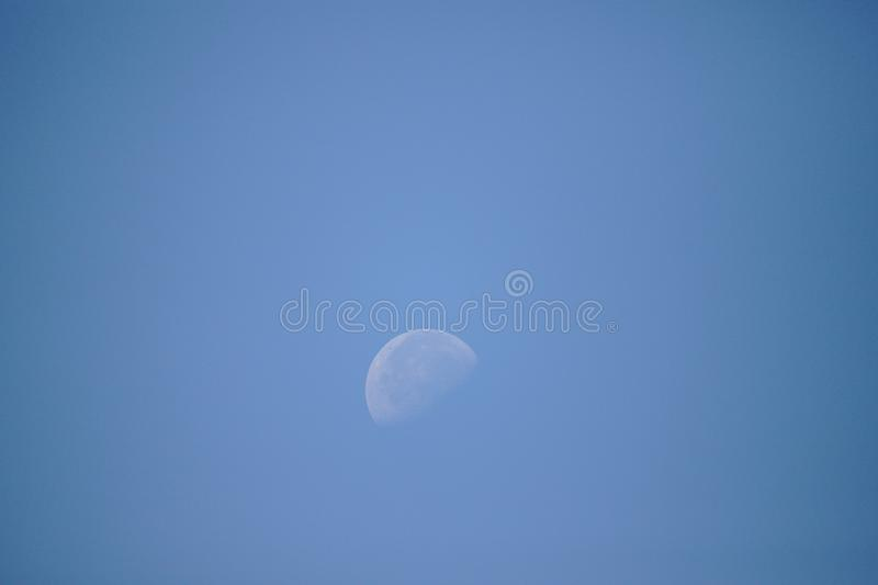 Half moon in the sky during daylight stock photos