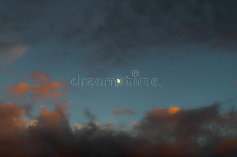 Half Moon at sunset. Surrounded by rainy clouds stock photo