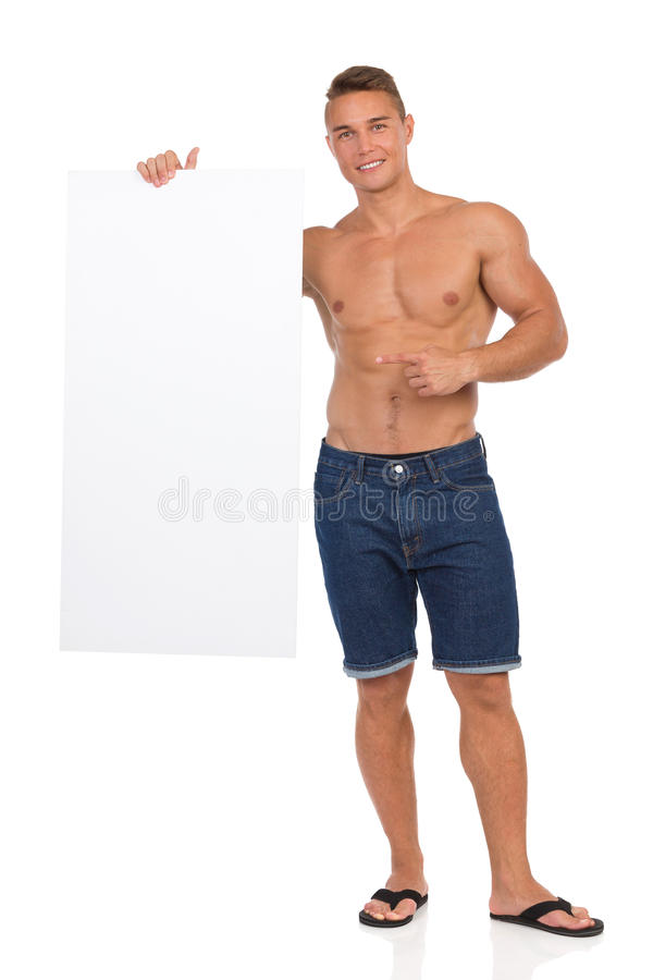 Half Naked Fit Man Holding Poster And Pointing. Half naked fit man in jeans shorts and black flip-flops standing, holding white placard, smiling and pointing stock photography