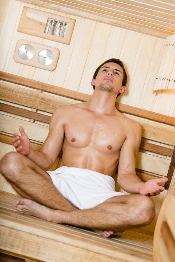 Half-naked man relaxing in asana in sauna