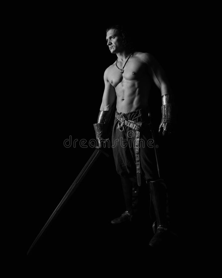 Half-naked man with a sword in medieval clothes stock photo