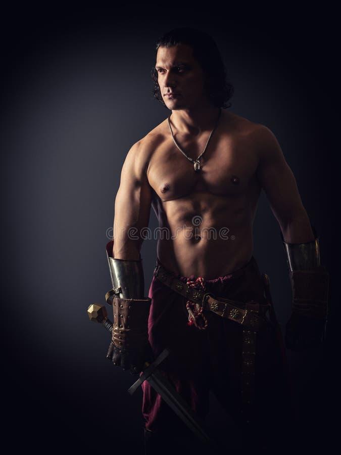 Half-naked strijder met een zwaard in middeleeuwse kleren stock afbeeldingen